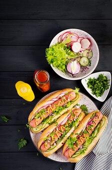 暗い木製のテーブルにソーセージ、キュウリ、大根、レタスのホットドッグ。夏のホットドッグ。上面図