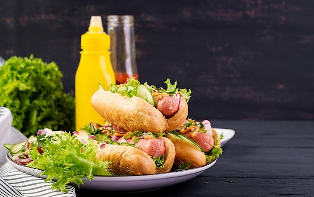 暗い木製のテーブルにソーセージ、キュウリ、大根、レタスのホットドッグ。夏のホットドッグ。