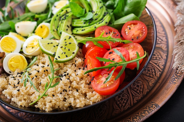 ダイエットメニュー。新鮮な野菜のヘルシーサラダ-トマト、アボカド、ルッコラ、卵、ほうれん草、キノアのボウル