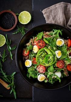 ダイエットメニュー。新鮮な野菜のヘルシーサラダ-ボウルにトマト、アボカド、ルッコラ、卵、ほうれん草、キノア。平干し。上面図。