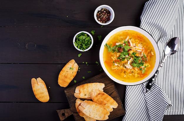 Суп из красной чечевицы с куриным мясом и овощами крупным планом на столе. здоровая пища. вид сверху