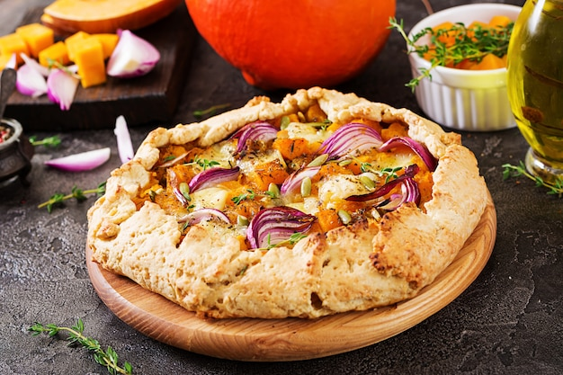 暗いテーブルの上のカボチャとモッツァレラチーズのガレットパイ。感謝祭の日の食べ物。