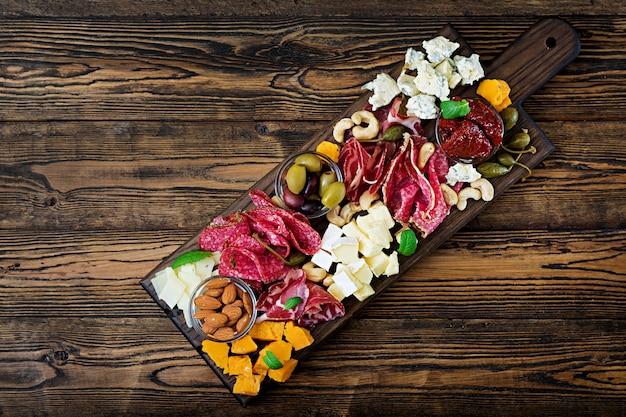 ベーコン、ジャーキー、ソーセージ、ブルーチーズ、木製のテーブルのブドウの前菜ケータリング大皿。上面図