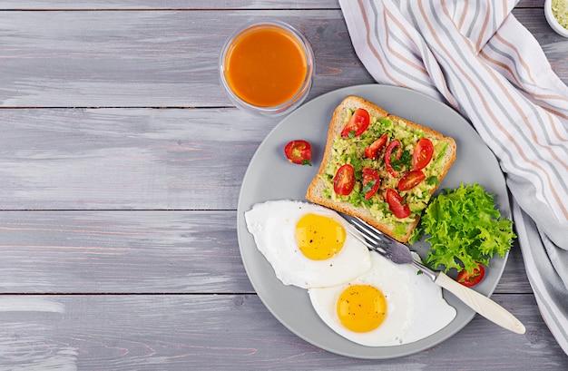 朝ごはん。目玉焼き、野菜サラダ、焼きアボカドサンドイッチ。上面図