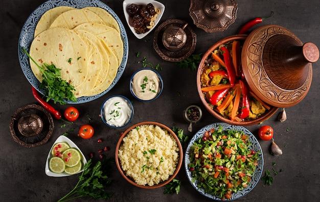 モロッコ料理。伝統的なタジン料理、クスクス、素朴な木製のテーブルに新鮮なサラダ。タジン鶏肉と野菜。アラビア料理。上面図。平置き