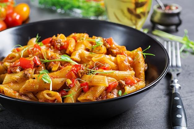 肉とトマトソースのペンネパスタ、暗いテーブルの上のエンドウ豆の芽で飾られたトマト。