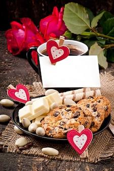 ホワイトチョコレート、アーモンド、クッキーとコーヒーのカップ