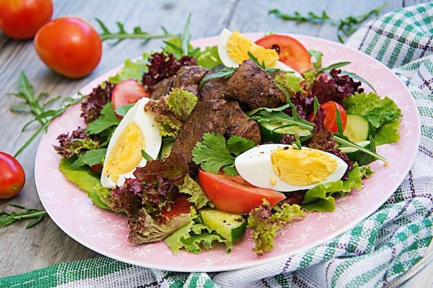 Теплый салат из куриной печени, помидоров, огурцов и яиц. здоровый ужин. диетическое меню