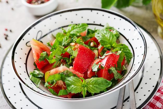 ボウルにバジルと松の実のトマトサラダ-健康的な菜食主義者ビーガンダイエット有機食品前菜。