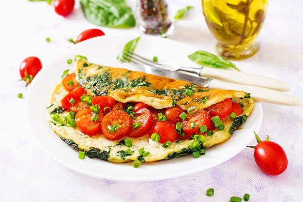 白い皿にトマト、ほうれん草、ねぎのオムレツ。
