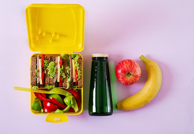 Здоровый школьный обед с бутербродом с говядиной и свежими овощами, бутылкой воды и фруктами на розовой поверхности
