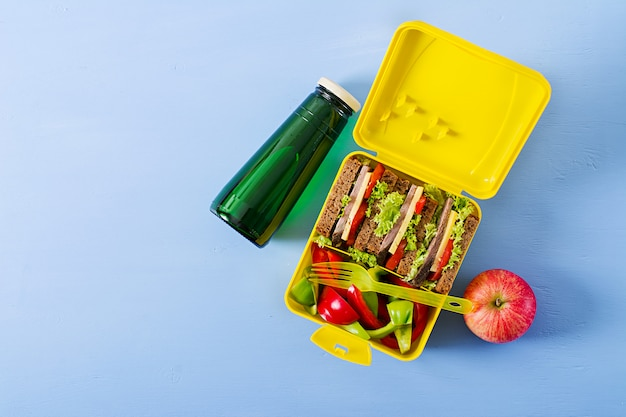 ビーフサンドイッチと新鮮な野菜、ボトル入り飲料水と果物の背景を持つ健康な学校ランチボックス