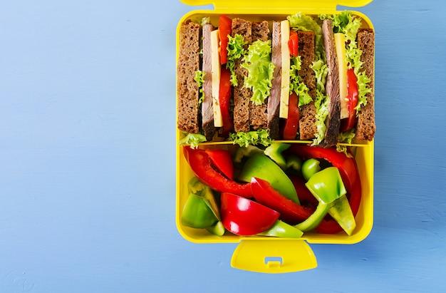 Здоровый школьный обед с бутербродом с говядиной и свежими овощами, бутылкой воды и фруктами