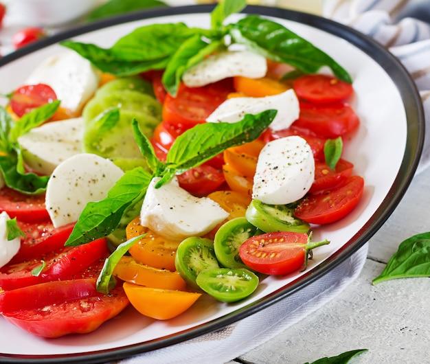 モッツァレラチーズ、トマト、バジルハーブは、白い木製のテーブルのプレートに残します。カプレーゼサラダ。イタリア料理。