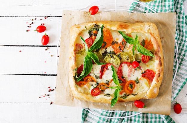 白い木製のテーブルにモッツァレラチーズ、トマト、バジルのおいしいパイ。おいしい料理、地中海スタイルの前菜。上面図。平置き