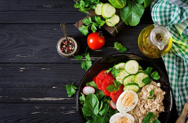 新鮮な野菜のヘルシーサラダ-トマト、キュウリ、大根、卵、ルッコラ、ボウルにオートミール。ダイエット食品。平干し。上面図