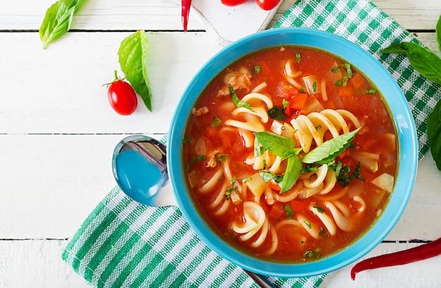 Минестроне, итальянский овощной суп с макаронами. суп томатный. веганская еда. вид сверху. квартира лежала.
