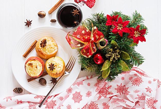 白いテーブルの上のクリスマスのカッテージチーズ、レーズン、アーモンドを詰めた焼きりんご。クリスマスフードデザート。