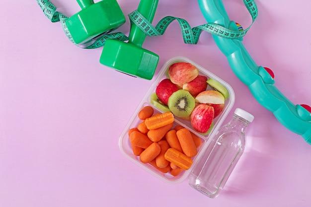ジムの設備。健康食品。コンセプトの健康食品とスポーツライフスタイル。ベジタリアンランチ。ダンベル、水、果物はピンクの表面に。上面図。平置き