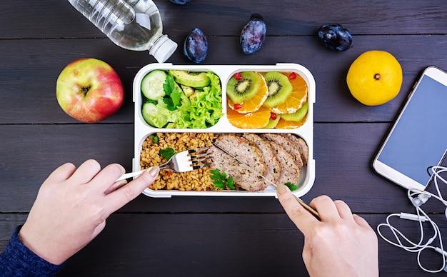木製のテーブルにブルガー、肉、新鮮な野菜、果物とヘルシーなランチを食べている手を示す平面図です。フィットネスと健康的なライフスタイルのコンセプト。弁当箱。上面図