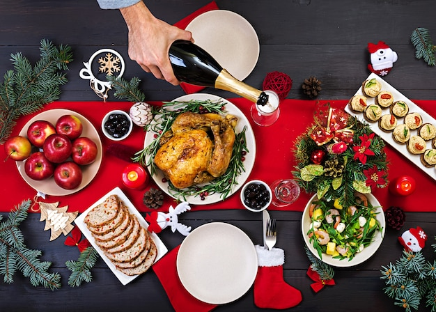 焼き七面鳥。クリスマスディナー。クリスマステーブルには七面鳥が添えられ、明るい見掛け倒しとキャンドルで飾られています。フライドチキン、テーブル。家族との夕食。上面図