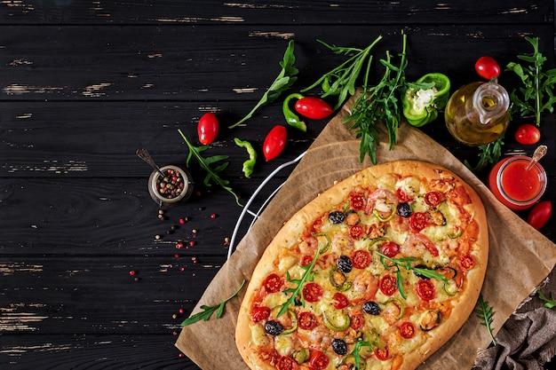 おいしいシーフードエビとムール貝のピザ、黒い木製のテーブル。イタリア料理。上面図