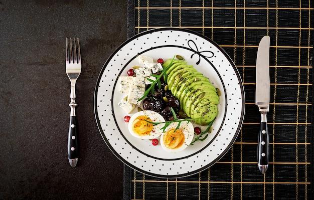 Полдник или полезный завтрак - тарелка голубого сыра, авокадо, вареного яйца, маслин на черной поверхности. вид сверху