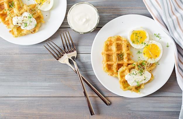 Здоровый завтрак или перекус. картофельные вафли и вареное яйцо на серый деревянный стол. вид сверху. плоская планировка