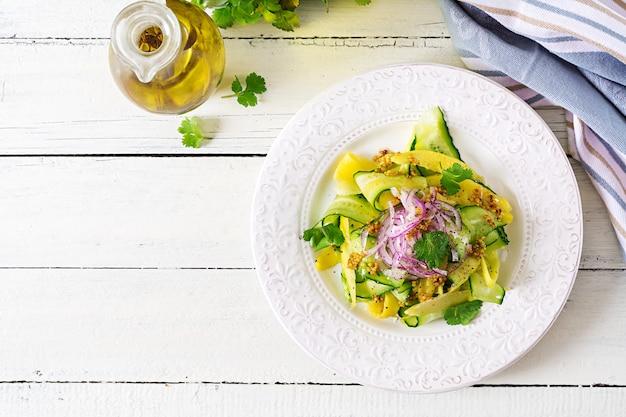 健康的なビーガンサラダマンゴー、キュウリ、コリアンダー、赤玉ねぎの甘酸っぱいソース。タイ料理。健康食。上面図。平置き
