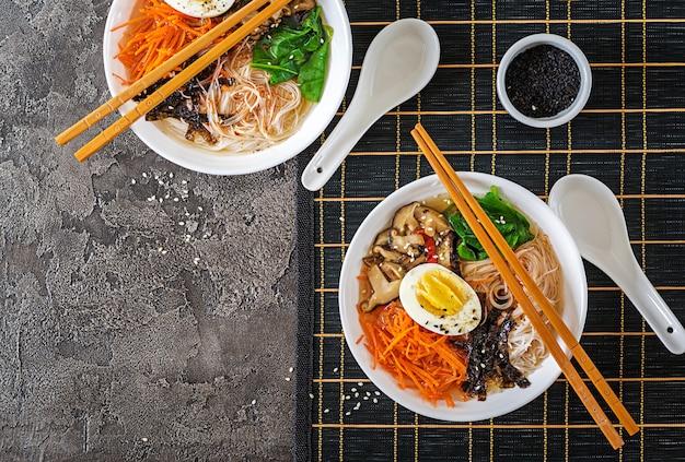 しいたけ、にんじん、ゆで卵の麺スープのベジタリアンボウル。日本食。上面図。平置き