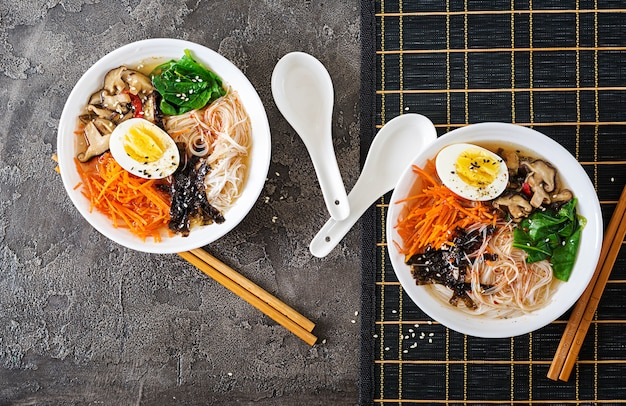 Диетическая вегетарианская миска супа с лапшой из грибов шиитаке, моркови и вареных яиц. японская еда. вид сверху. плоская планировка