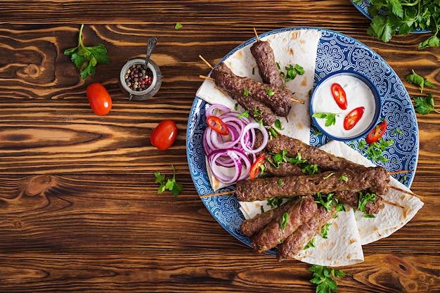Турецкий и арабский традиционный рамадан микс кебаб. кебаб адана, курица, баранина и говядина на лаваш с соусом. вид сверху