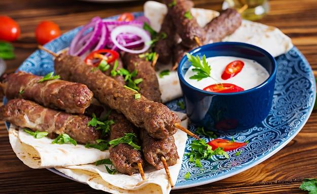 トルコとアラビアの伝統的なラマダンミックスケバブプレート。ケバブのアダナ、鶏肉、ラム肉、牛肉のラバッシュパンソース添え。上面図