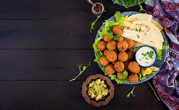 ファラフェル、フムス、ピタ。暗い背景に中東料理またはアラビア料理。ハラル食品。上面図。コピースペース