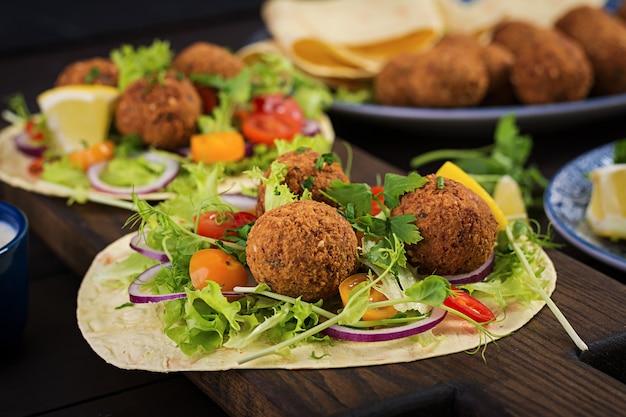 Обертывание из тортильи с фалафелем и свежим салатом. веганские тако. вегетарианская здоровая пища.