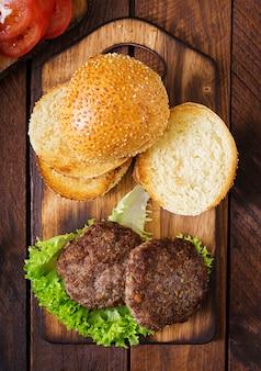 Ингредиенты для бутерброд - гамбургер с говядиной, солеными огурцами, помидорами и красным луком на деревянных фоне. вид сверху