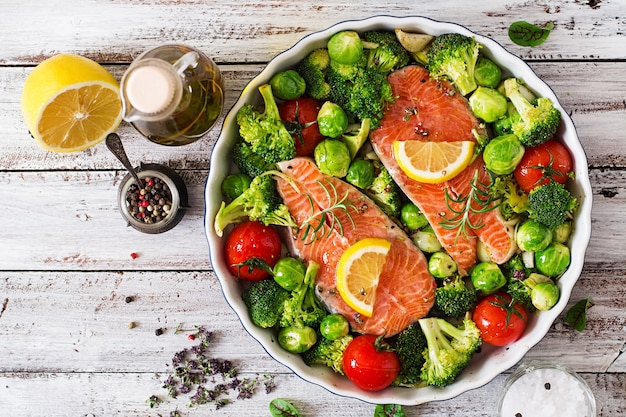 生サーモンステーキと素朴なスタイルの明るい木製の背景で調理するための野菜。上面図