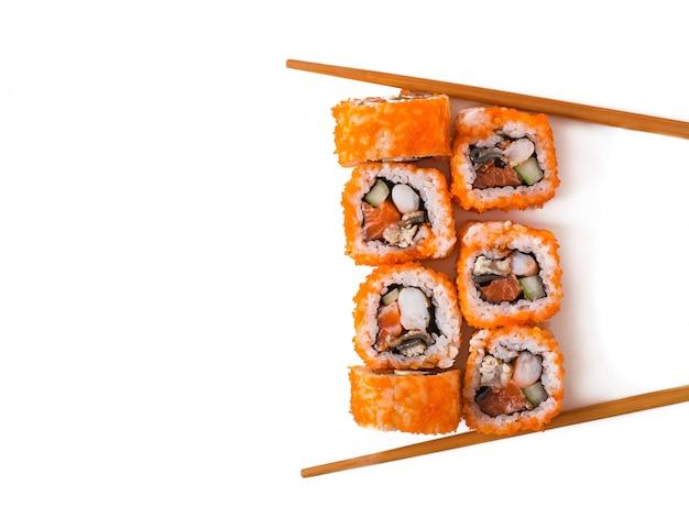 白い背景に分離された伝統的な新鮮な日本の寿司ロール。上面図