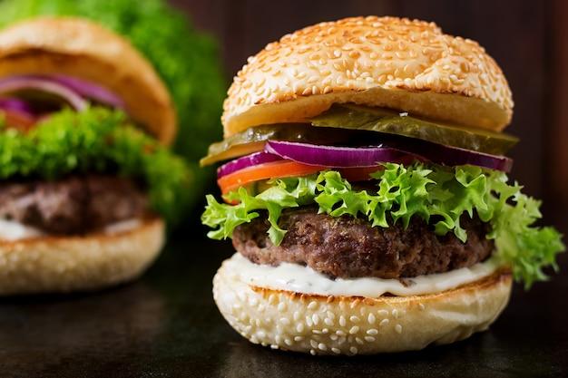 Большой бутерброд - гамбургер с говядиной, солеными огурцами, помидорами и соусом тар-тар на черном фоне.