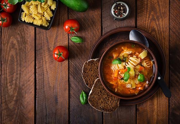 ミネストローネ、木製のテーブルにパスタとイタリアの野菜スープ。上面図