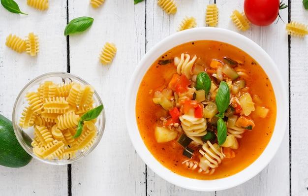 Минестроне, итальянский овощной суп с макаронами на белом деревянном столе. вид сверху