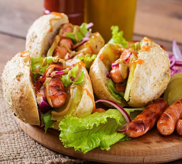 ホットドッグ-ピクルス、赤玉ねぎ、木製の背景にレタスのサンドイッチ