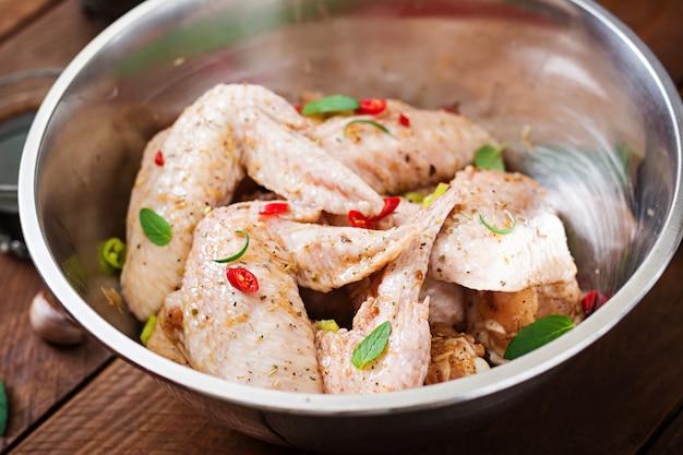 Сырые маринованные куриные крылышки, приготовленные в азиатском стиле с медом, чесноком, соевым соусом и зеленью