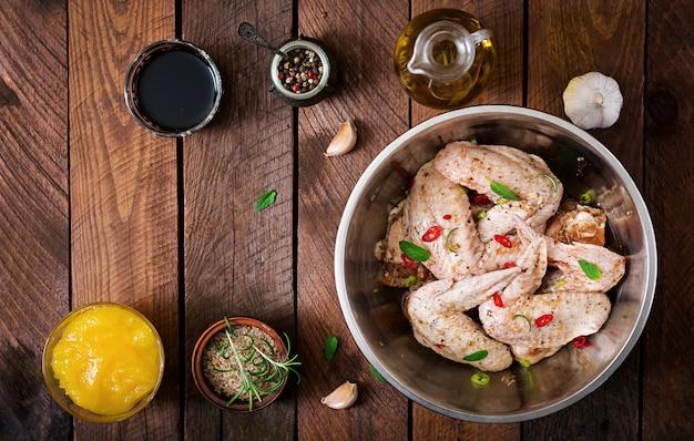 Сырые маринованные куриные крылышки, приготовленные в азиатском стиле с медом, чесноком, соевым соусом и зеленью. вид сверху