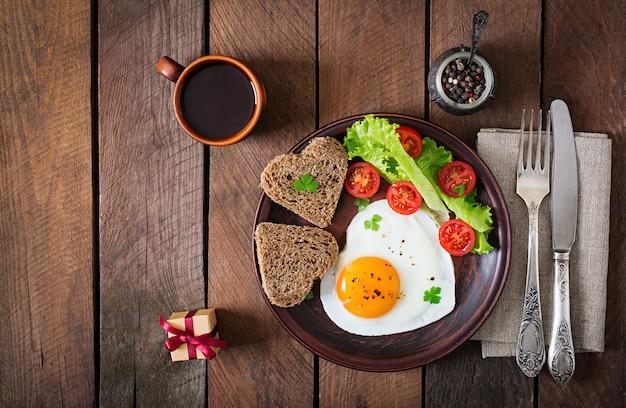 バレンタインデーの朝食-目玉焼きとハート型のパンと新鮮な野菜。上面図