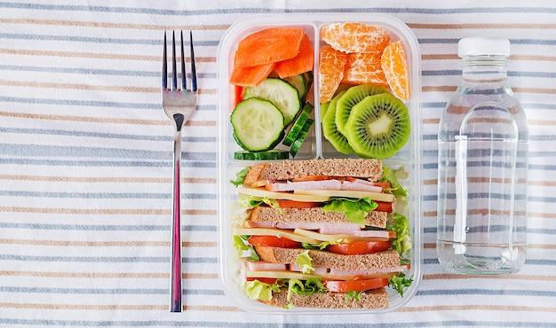 Коробка школьного обеда с бутербродом, овощами, водой и фруктами на столе. концепция здорового питания. квартира лежала. вид сверху