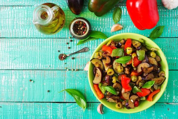 Горячий острый тушеный баклажан, сладкий перец, оливки и каперсы с листьями базилика. вид сверху