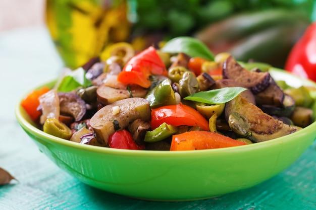 Горячий острый тушеный баклажан, сладкий перец, оливки и каперсы с листьями базилика.