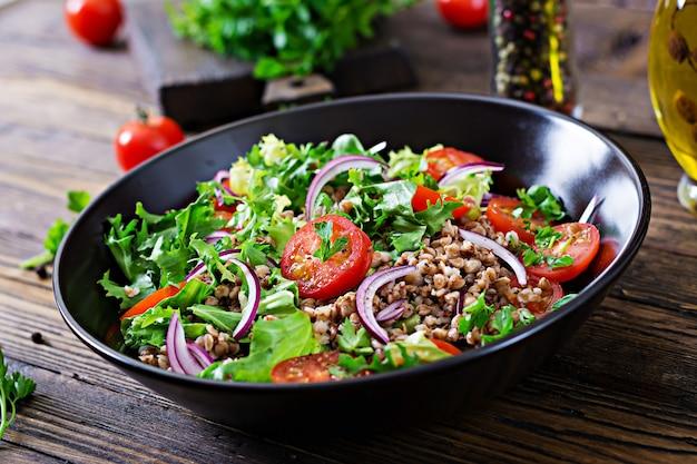 Гречневый салат с помидорами черри, красным луком и зеленью. веганская еда. диетическое меню.