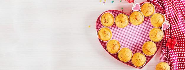 かぼちゃのマフィン。バレンタインデーの装飾が施されたカップケーキ。平干し。バナー。上面図。
